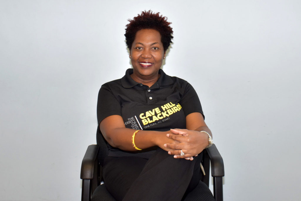 Robena Nicholls sits in a chair, looking straight at the camera. She is wearing a polo shirt advertising The University of the West Indies Cave Hill Campus. Her legs are crossed and her hands are folded on her knee.