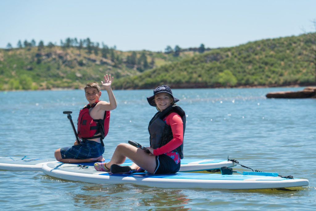 Two kids paddle boarding at horsetooth reservoir.
