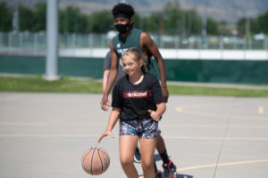 Camper and counselor playing basketball