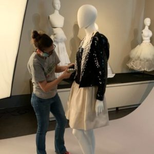 Dr. Knowles dressing a Scaasi outfit on photography set.
