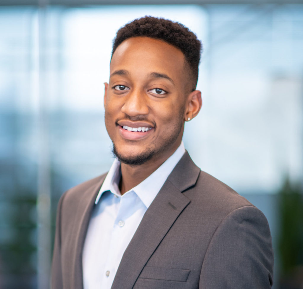 "De'Ohndre ""Dre"" Jackson smiles in a corporate office wearing a gray blazer and a blue button down shirt. Dre is a black man with medium-dark brown skin and a medium length fade haircut."