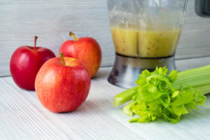 Apples and celery next to a blender