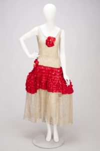 1920's flapper dress, with red waistline and red flower at the bust, gold coloring elsewhere.