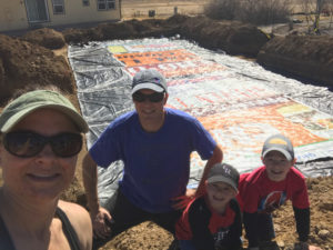 Cody Farmer, wife Lisa and 2 sons in front of new build project