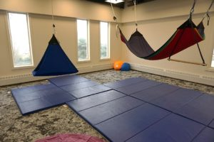 Hammocks hanging from ceiling with mats on floor in playground lab