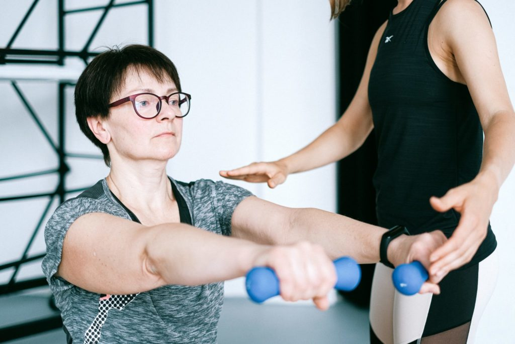 Middle aged woman exercising with instructor