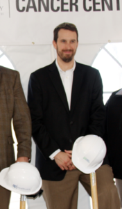 Eric Dimmick standing with a shovel and a construction helmet