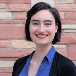 Katie Brown is wearing a blue collared shirt and black blazer, standing in front of a stone wall