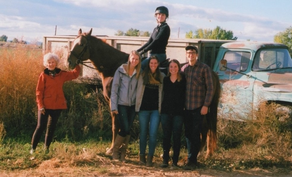 Rebecca Lassell and friends standing by a horse and its rider