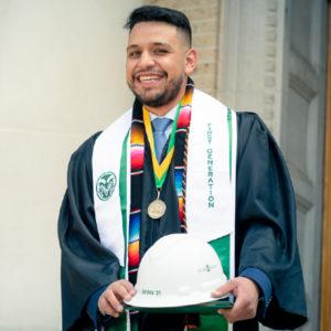 Bryan Flores Amezquita in graduation regalia holding his hardhat