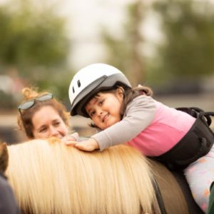 A girl on a horse with a helper