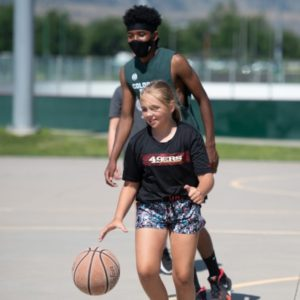 A camper with a counselor playing basketball