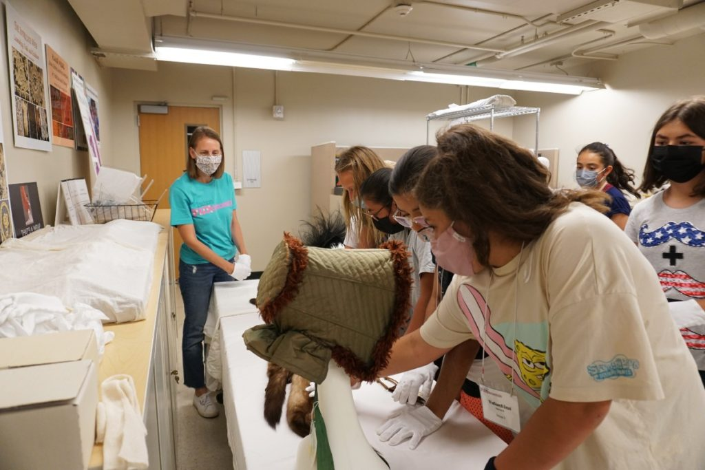 Girls examining historic textiles