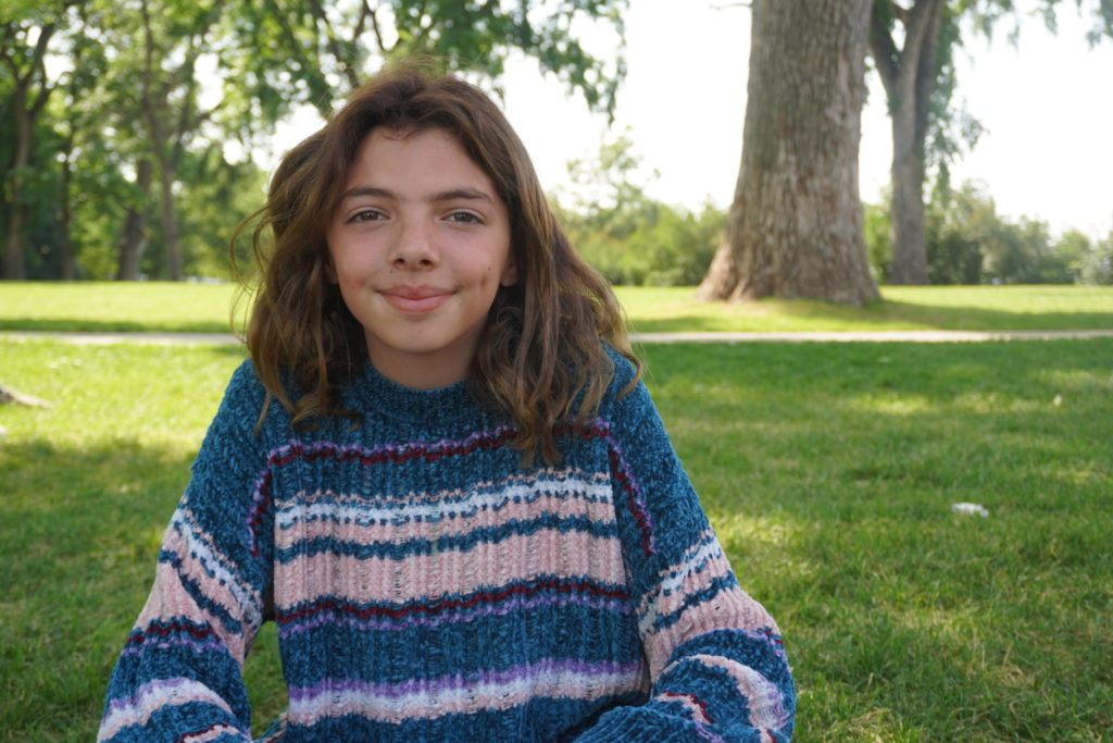A young girl smiles while wearing a sweater
