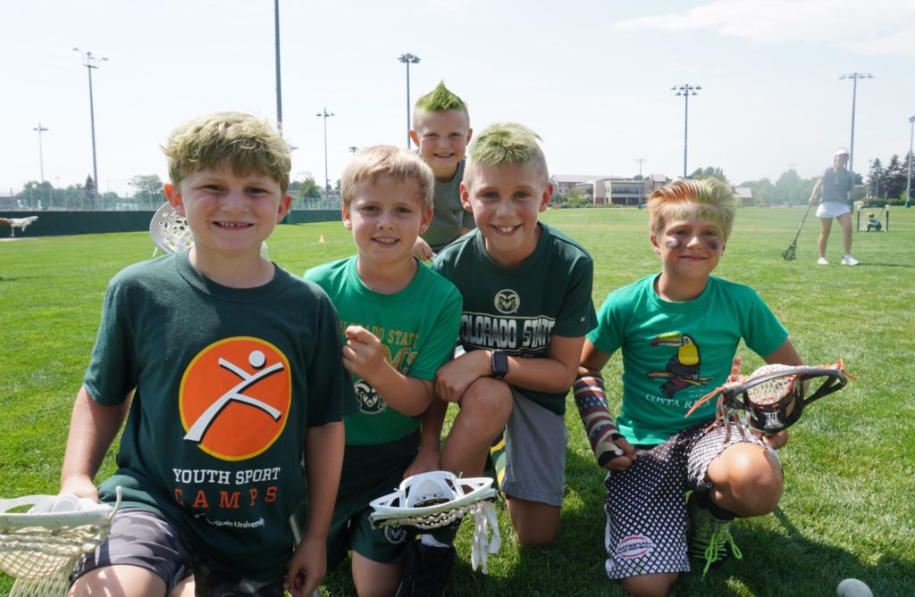 Five boys smile while holding lacrosse sticks.
