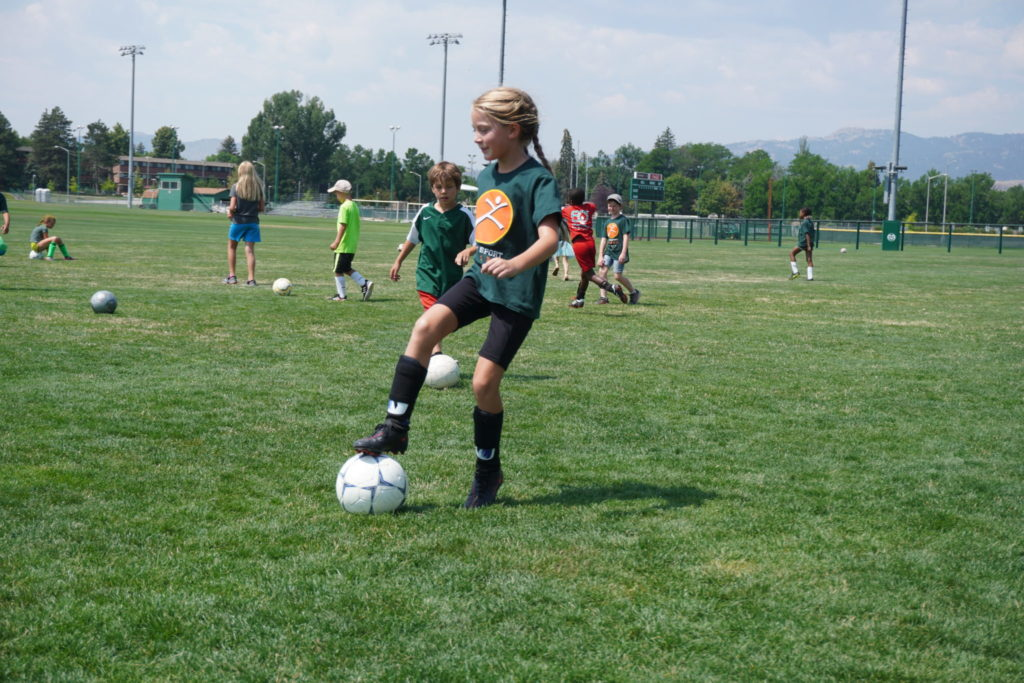 A young girl plays soccer in a field.