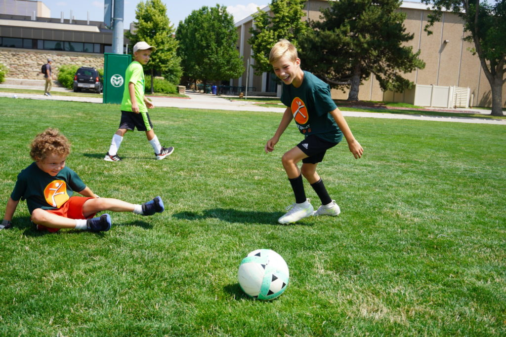 Two boys play soccer together, they both smile.