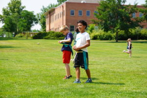 Two boys smile in a field while playing capture the flag.
