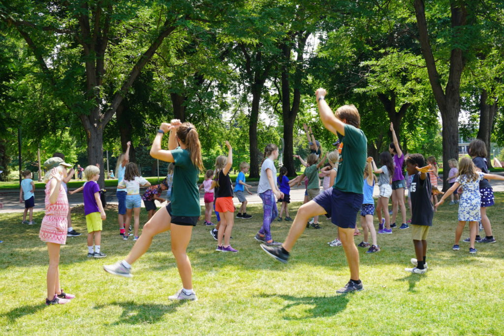 A group of children and CSU students do a coordinated dance