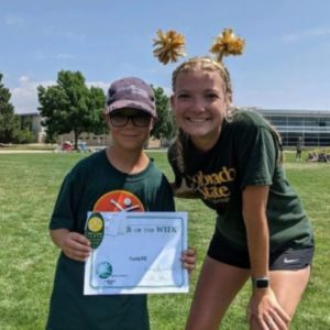 Student Kendall Crepeau poses with a camper holding an achievement certificate.