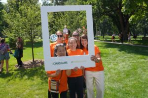 Jen Aberle poses with other staff members outdoors holding a photo frame