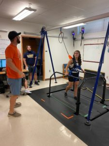Jordan Acosta walks on a treadmill attached to research apparatuses.