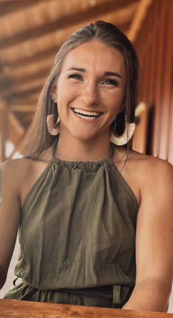Jordan Acosta smiles in a green top.