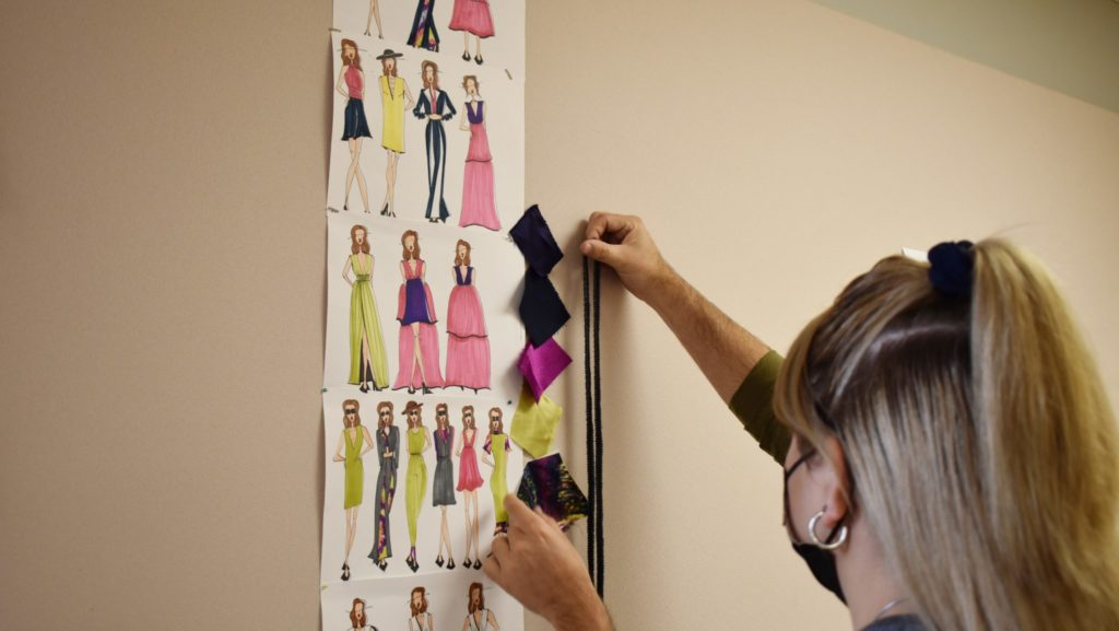 Students hold up sewing notions to compare to fabric samples pinned by fashion sketches.