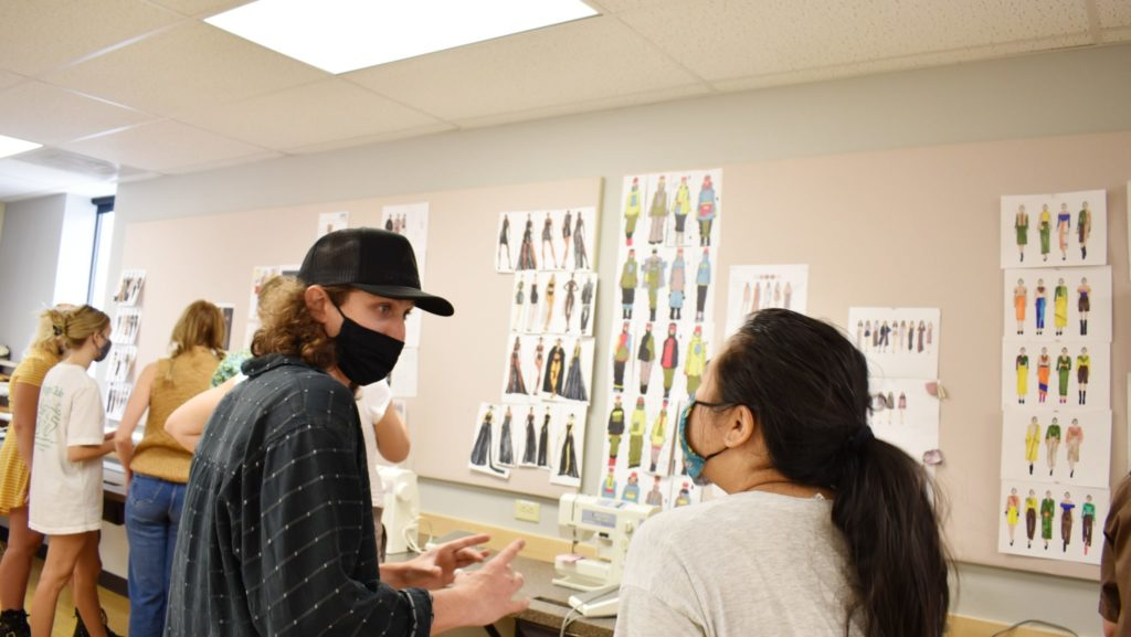 Two students discuss the fashion design sketches on the wall near them.