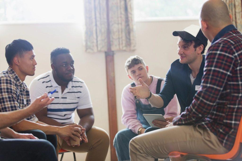 Men sitting in circle talking