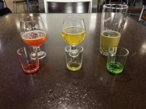 Three flavor shots in small glasses: red, yellow, and green.