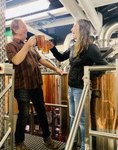 Jeff Biegert and Katie Fromuth smile and toast their pints of beer together