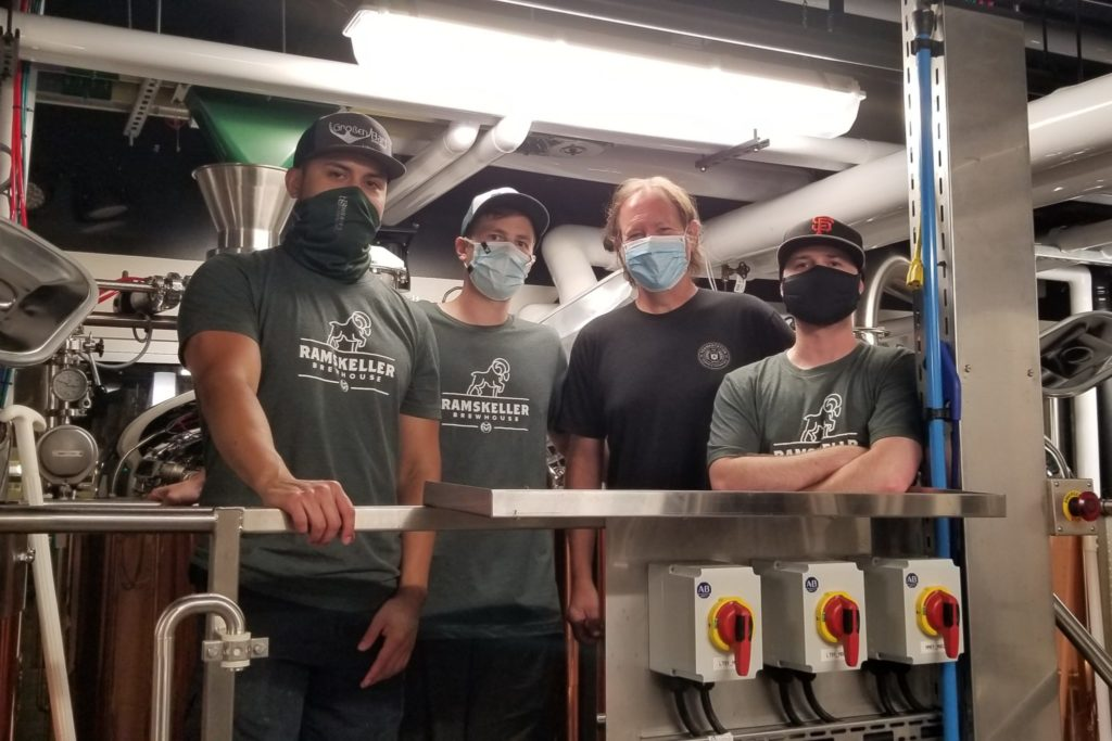 Jeff Biegert with a group of students smiling behind masks at the Brewery